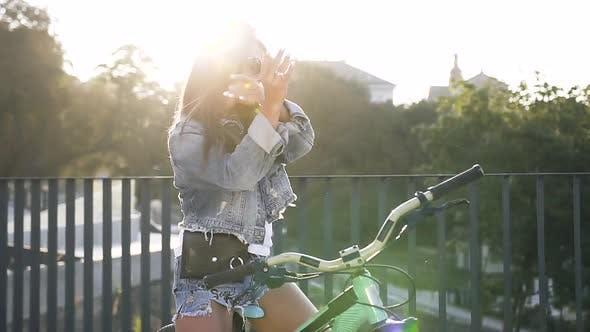 Cover Image for Woman with Long Hair in Fashion Jeans Clothes Sitting on Her Bike Sings and Dances