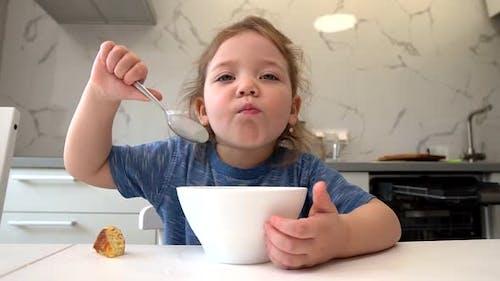 Ein kleines Kind isst gesundes Essen von einem weißen Teller