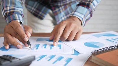 Man Hand with Pen Analyzing Bar Chart on Paper