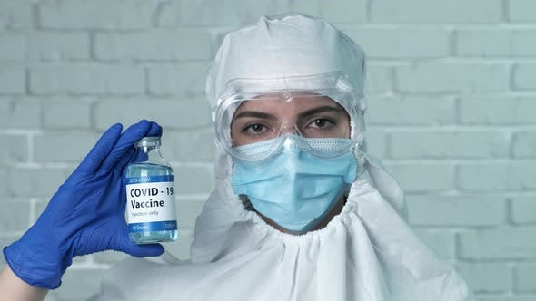 Thumbnail for Female Doctor with Protective Medical Mask Holding Bottle with Covid-19 Vaccine Close-up. Prevention