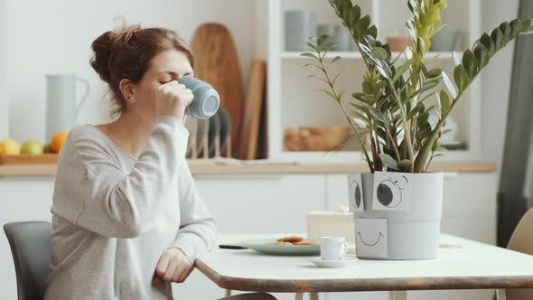 Young Woman Drinking Tea, Using Phone and Watering Plant at Home