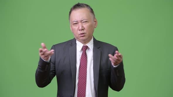 Thumbnail for Mature Confused Japanese Businessman Shrugging Shoulders
