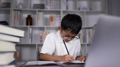 Boy thinking and doing homework at home.