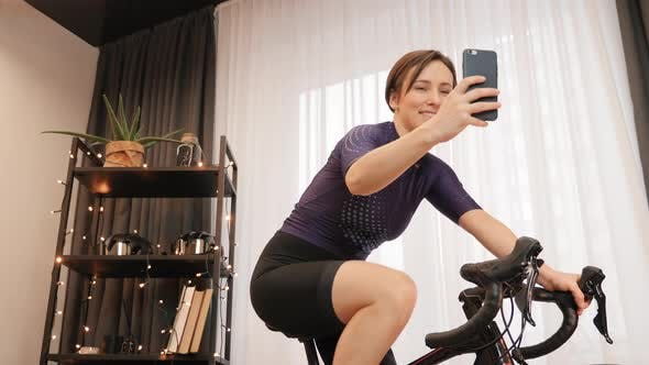 Female athlete takes selfies on smartphone while cycling on exercise bicycle. Indoor cycling