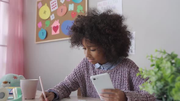 Afrikanisches Kind Schulmädchen mit Handy-App Fernstudium zu Hause