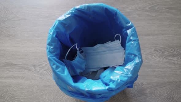 Throwing Away Single Use Medical Face Mask and Gloves
