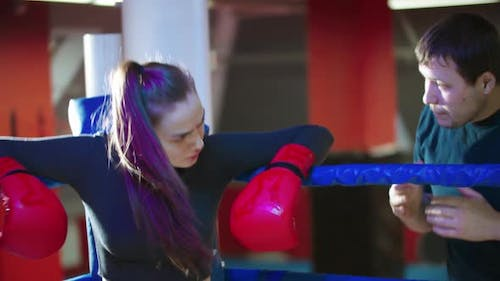 An Attractive Young Woman Resting on the Boxing Ring and Her Trainer Talks To Her