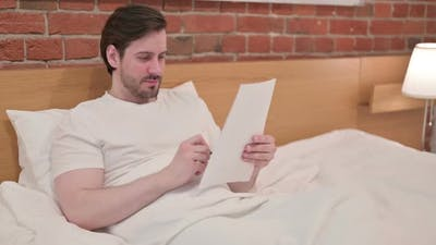 Young Businessman Reading Documents in Bed