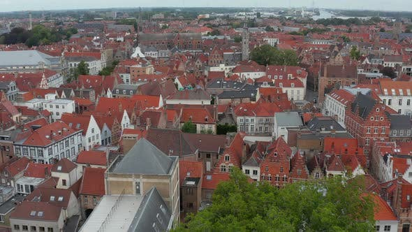 Thumbnail for Cityscape Over Bruges, Belgium with Red Rooftops with Churches From Aerial Perspective
