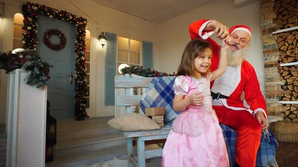 Thumbnail for Whirling Little Girl and Cheerful Santa Claus.
