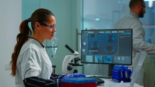 Biotechnology Scientist Researching in Laboratory Using Microscope