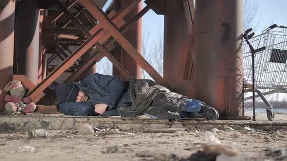 Cover Image for Cold Homeless Beggar Sleeping Under Bridge