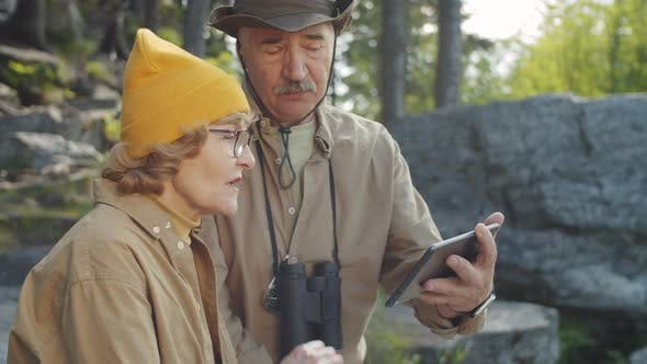 Senior Couple Discussing Hiking Route on Tablet