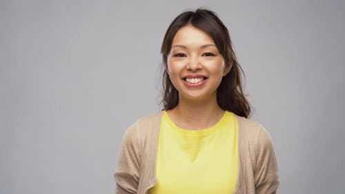 Portrait of Smiling Young Asian Woman in Cardigan