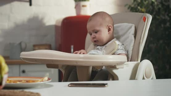 Thumbnail for Baby Playing in a High Chair