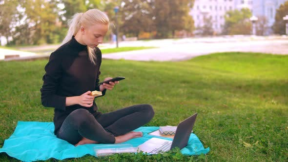 Thumbnail for Caucasian Girl Eats and Typing on Laptop Outdoor