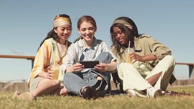 Multiethnic Girlfriends Resting on Grass in Summer