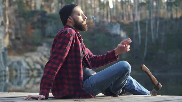 Cover Image for Bearded Guy Sit in the Forest Near River and Smoking Brown Cigar