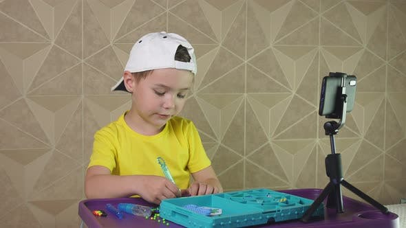 Child in a Baseball Cap Records a Video for the Internet. A Small Blogger Is Talking on Video