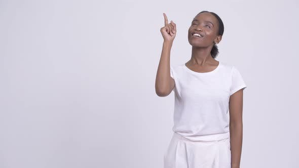 Thumbnail for Happy Young Beautiful African Woman Thinking While Pointing Up