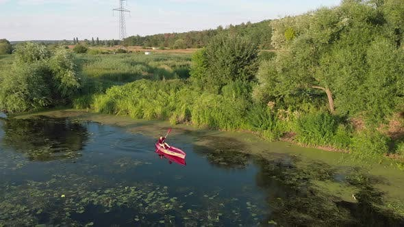 Thumbnail for Drone view of female kayaking on river at sunset. Sport rowing. Water tourism