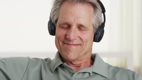 Happy senior man listening music blutetooth headphones
