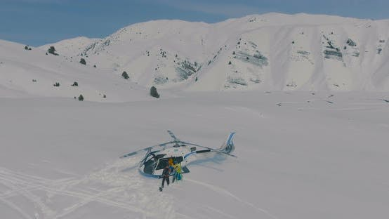Thumbnail for Aerial view Skiers go on landing a heliskiing helicopter standing in the snow in the winter mountain