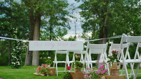 Cover Image for Green Lawn with Rows of White Wooden Chairs