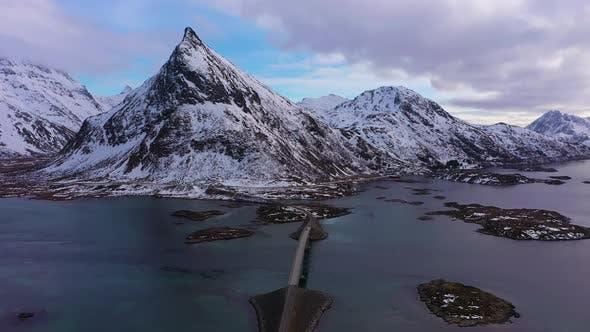 Fredvang Bridge and Volandstind Mountain in Winter. Lofoten, Norway. Aerial View