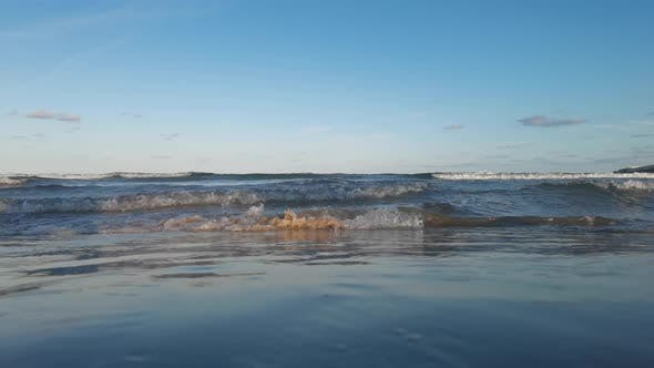 Low Angle Footage of Waves Breaking on Sand Beach