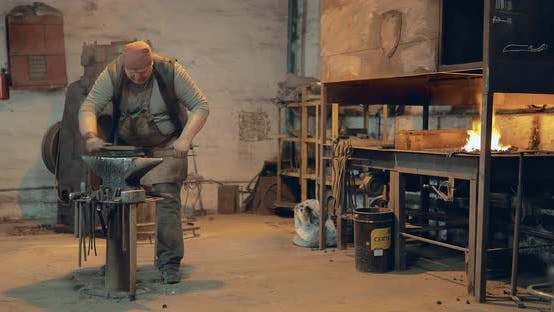 Brutaler Schmied holt das Holzbrett aus dem Ofen