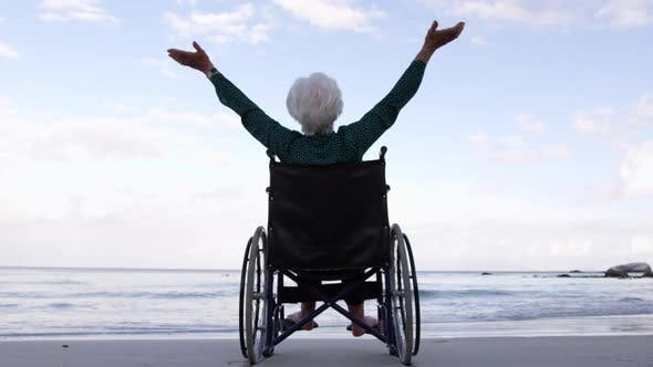 Thumbnail for Woman with arms outstretched on wheelchair at beach 4k