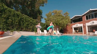 Mother And Daughter Jumping Into The Pool
