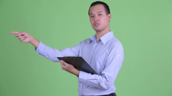 Thumbnail for Happy Asian Businessman Talking While Holding Clipboard