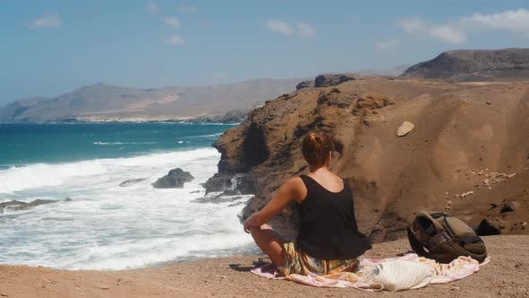 Girl Sitting On Cliff And Looks At The Ocean or Sea.Beautiful Woman Sitting On Rock On Canarian