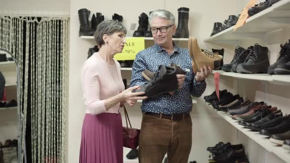 Thumbnail for Irritated Senior Wife Putting Footwear Back on Shelves and Talking To Husband Holding Last Shoe
