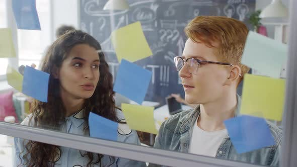 Thumbnail for Creative Millennials Arranging Sticky Notes on Glass Wall in Office