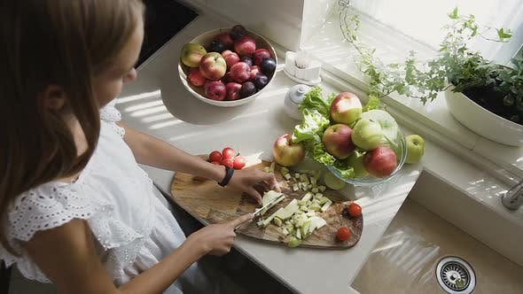 Cover Image for Attractive Blonde Girl in White Dress is Preparing Fruits Salad in the Kitchen