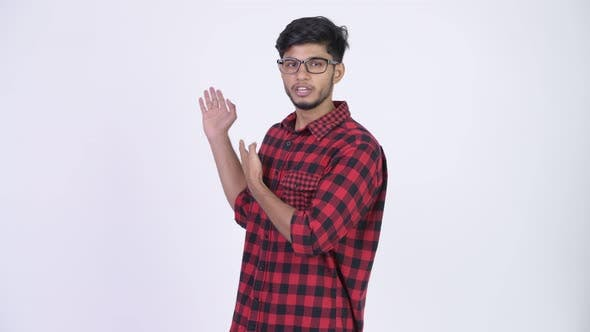 Thumbnail for Young Handsome Bearded Indian Hipster Man Presenting Something