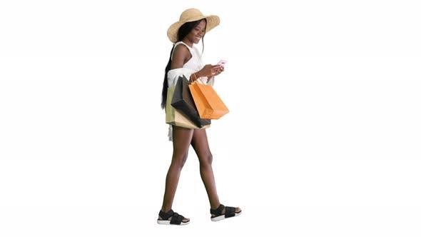 Glückliche afrikanisch-amerikanische Frau mit Hut, die spaziert und ein Telefon auf weißem Hintergrund benutzt.