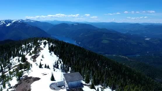 Flying Around Snow-Covered Sullivan Peak Lookout Revealing Sullivan Lake in Background