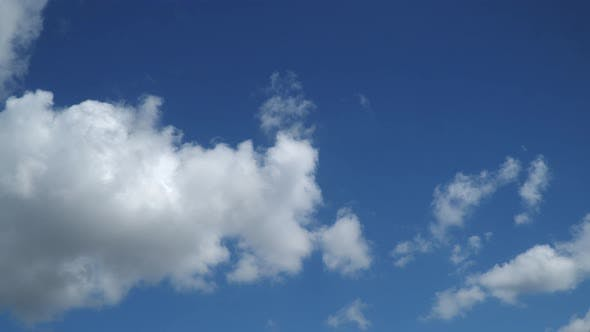 Time-lapse. The movement of white clouds against the blue sky