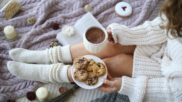 Thumbnail for Woman's Hands And Feet In Sweater And Knit Cozy Beige Socks Holding Cup Of Hot Chocolate And Cookies