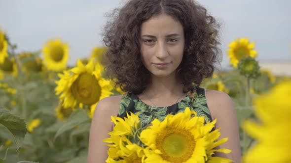 Thumbnail for Portrait of Beautiful Curly Playful Girl Looking at the Camera Smiling Standing in the Sunflower