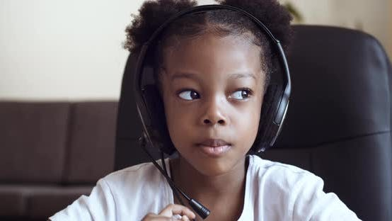 Thumbnail for Funny African Girl in Headphones Speaks in Webcam, Child Answers Video Call, Speaks in Microphone on