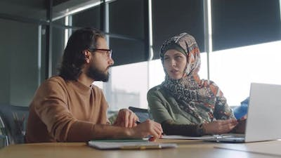 Arab Businessman Talking with Female Colleague in Hijab
