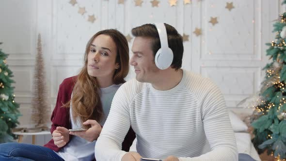 Happy Couple Enjoying Music in Earphones Together