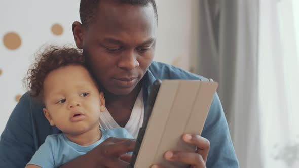Thumbnail for African Man with Toddler Using Tablet