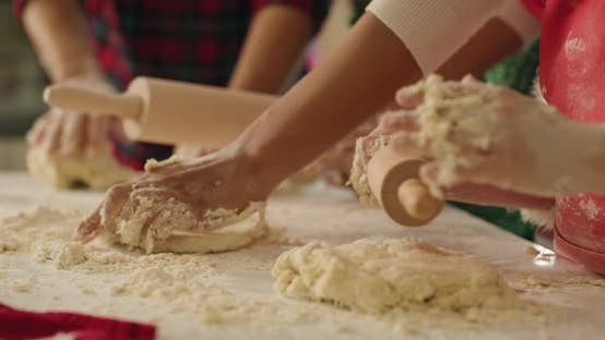 Thumbnail for Handheld view of family rolling the dough for Christmas cookies