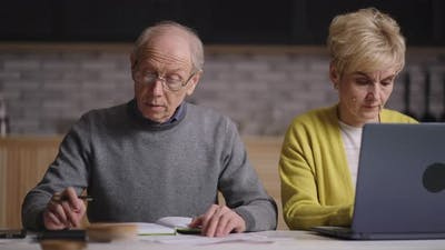 Old Retirees are Calculating Expenses and Revenue Financial Planning and Saving Family Budget Old